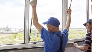 craftsmen workers install window in house rattle with a special rubber hammer